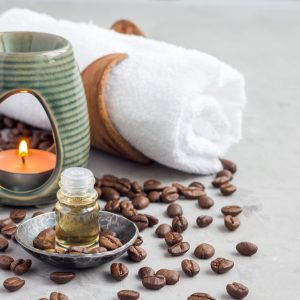 spa towel with candle oil and coffee beans