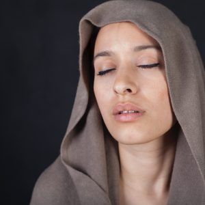 Woman covered head meditating